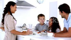 Mother chatting to children at family breakfast and pouring milk