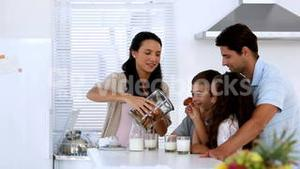 Mother giving cookies to her family with milk