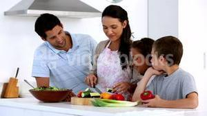 Mother showing children how to chop vegetables