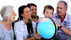 Extended family looking at globe together