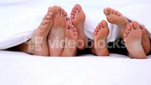 Familys feet peeking from under the covers
