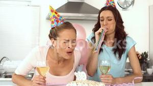 Woman blowing candle and celebrating her birthday with a friend