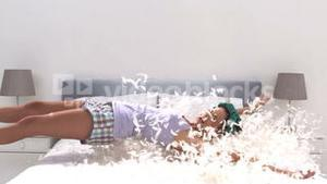 Cute woman falling on her bed full of pillow feathers