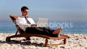 Unstressed businessman using laptop on the beach