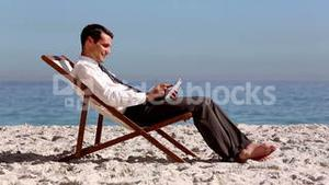 Smiling businessman using tablet and relaxing on the beach