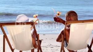 Couple drinking cocktail on the beach