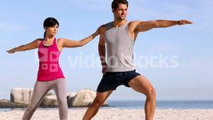Man and woman training on the beach