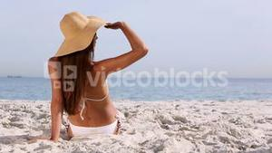 Beautiful brunette with hat tanning