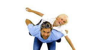 Son having a piggy back on his father on white background