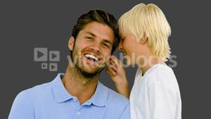 Son pinching the ear of his father on grey background