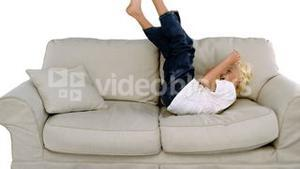Boy jumping on the sofa on white background