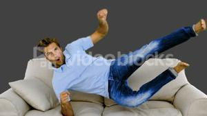 Man jumping on the sofa on grey background