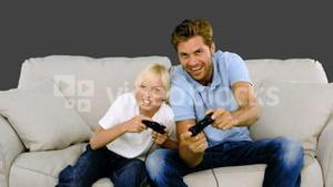 Father and son playing video games on grey background