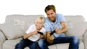 Father and son playing video games on white background
