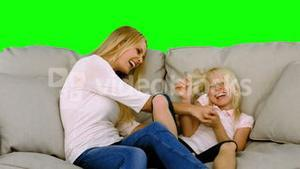 Mother and daughter tickling each other on sofa in slow motion
