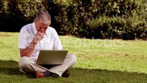 Mature man sat on the grass using his laptop