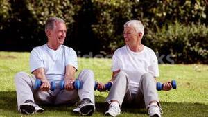 Mature couple sat on the grass lifting dumbbells