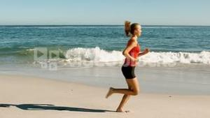 Woman with red tank top running on the beach