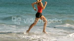 Happy woman running into the sea