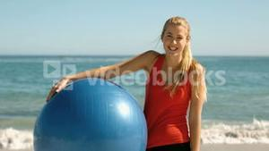 Happy woman holding gym ball on the beach