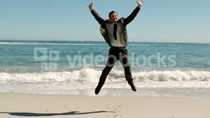 Attractive businessman jumping on the beach