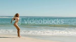 Blond woman jumping on the beach