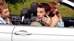 Parents on the phone in a convertible car