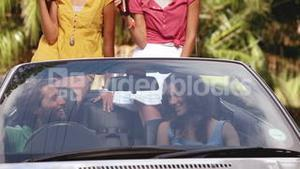 Group of friends drinking beer in a convertible car