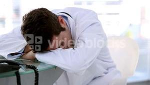 Young doctor sleeping on a desk