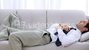 Businessman crashing down onto sofa