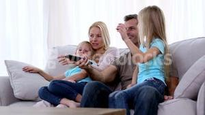 Family watching television on sofa