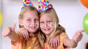 Twin sisters with thumbs up at birthday party