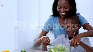 Mother teaching to her son how to mix salad
