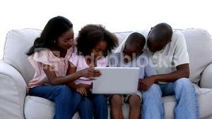 Family with laptop on a sofa