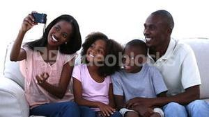 Family taking picture sitting on a sofa