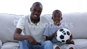 Father and his son watching football