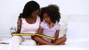 Mother and her daughter reading book