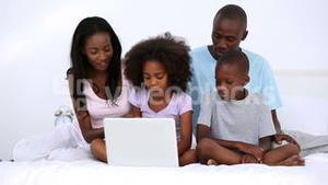 Family with laptop on a bed