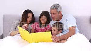 Family reading a storybook in the bed
