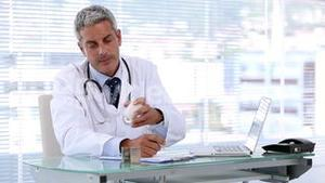 Doctor looking at pills while writing a prescription