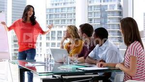Woman giving presentation to her colleagues
