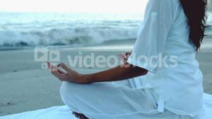 Woman relaxing on the beach practicing yoga