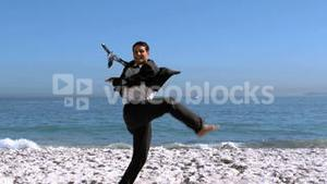 Businessman jumping and kicking on the beach