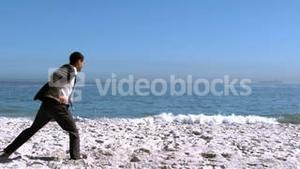 Businessman jumping then revolving on the beach