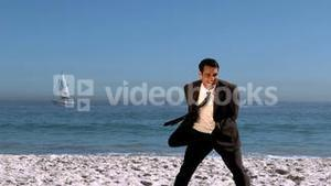 Attractive businessman playing with beachball