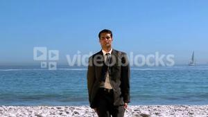 Funny businessman jumping and crossing the beach