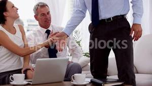Businessman shaking hands of business people
