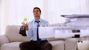 Happy businessman juggling with tennis ball