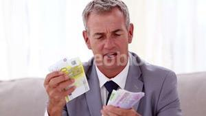 Happy businessman counting banknotes