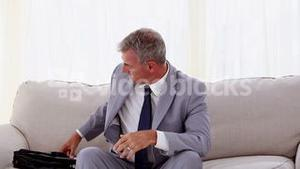 Businessman sitting on couch opening umbrella
